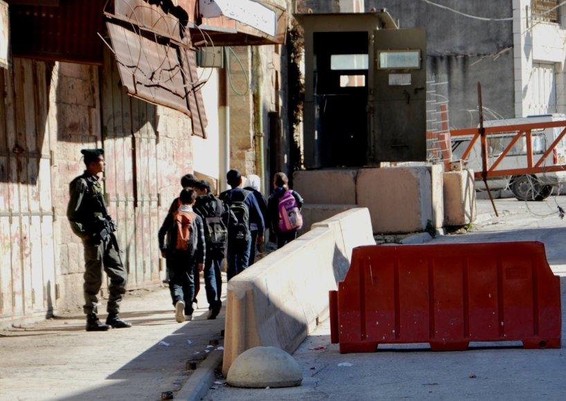 Kareivio prižiūrimi vaikai eina į mokyklą