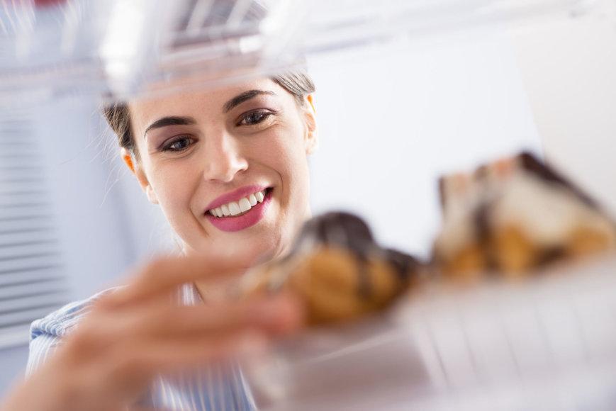 Moteris iš šaldytuvo ima pyragėlius