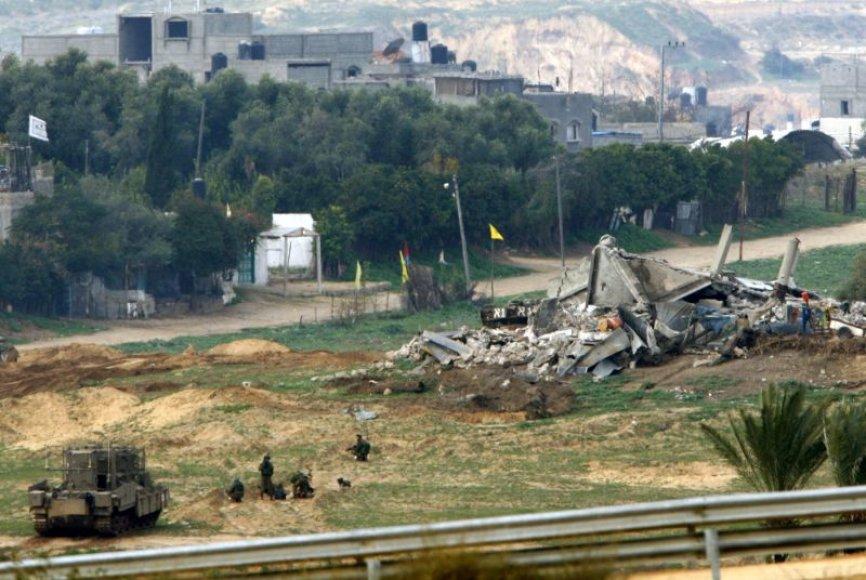 Izraelio kariai netoli sugriauto pastato
