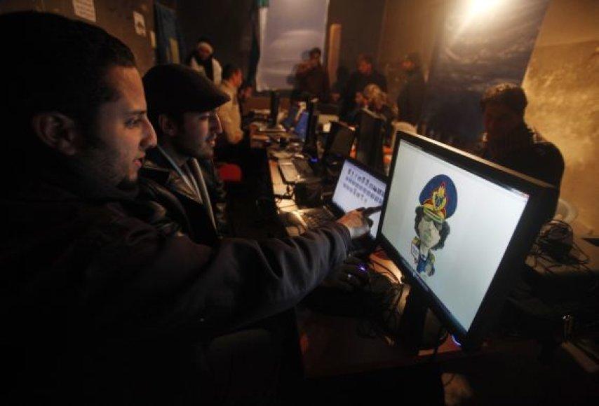 Protestuotojai Bengazyje, buvusioje saugumo būstinėje, kuria Muamaro Kadhafio karikatūrą.