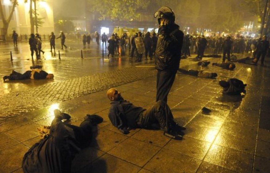 Ant prospekto grindinio guli policijos sulaikyti mitingo dalyviai.