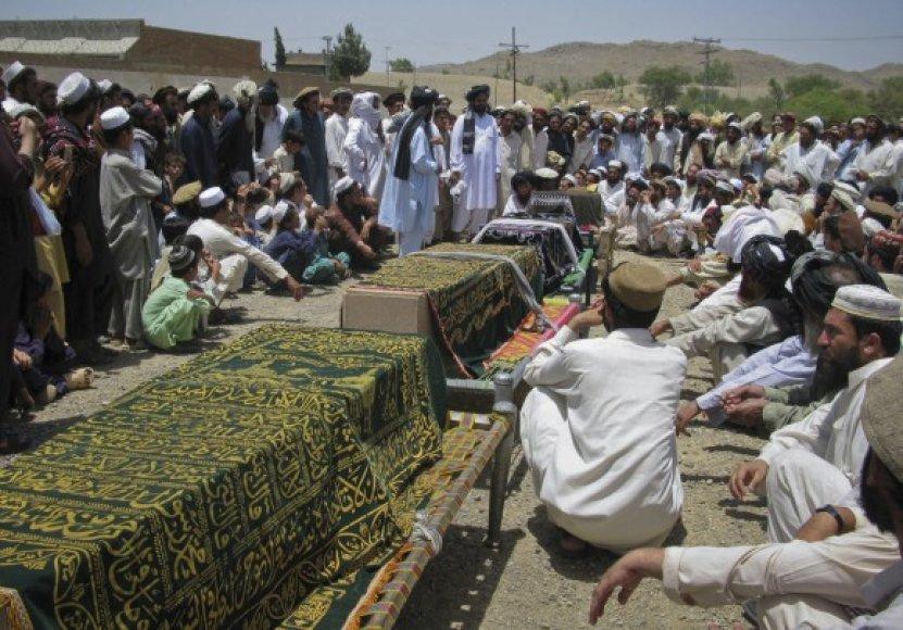 Pakistaniečiai laidoja žmones, žuvusius per bepiločio JAV lėktuvo ataką.
