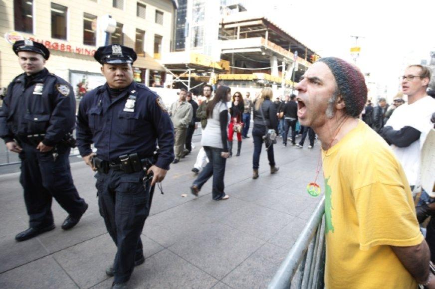Policininkai eina pro protestuotoją Zuccotti parke.
