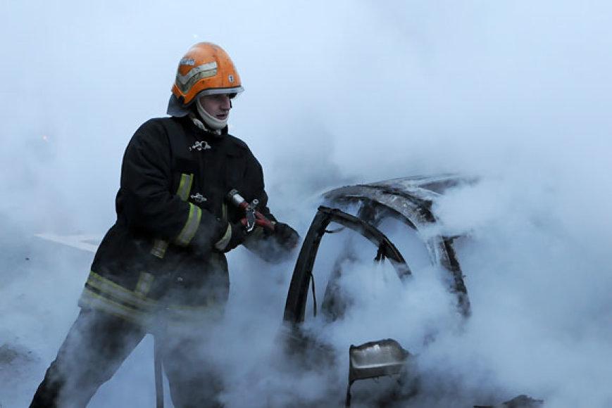 Ugniagesys gesina degantį automobilį