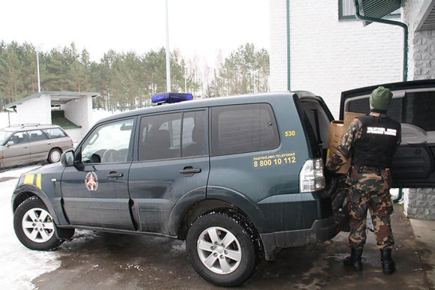 Pasieniečiai iš tarnybinio automobilio iškrauna sulaikytas cigaretes