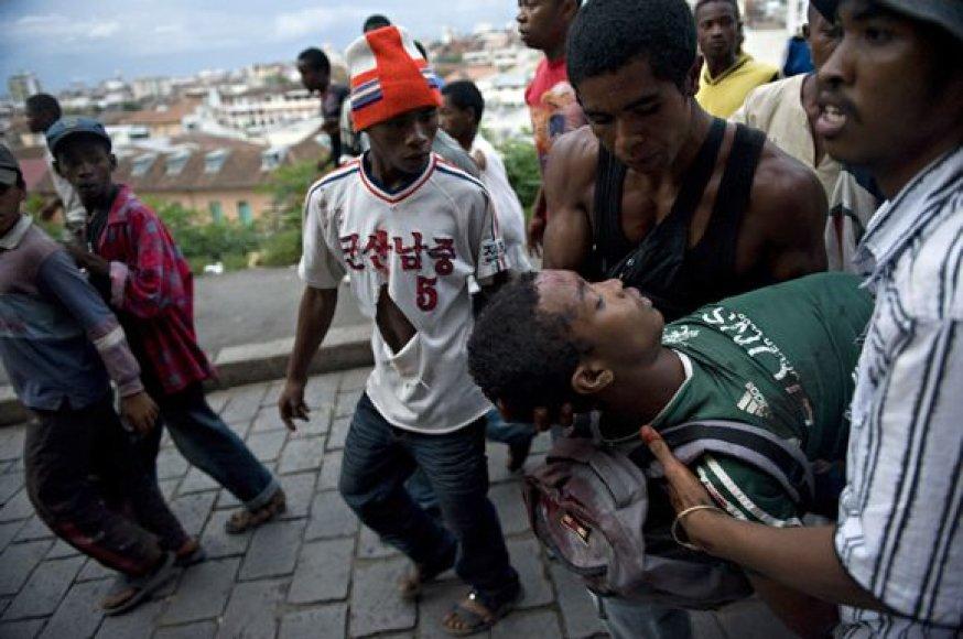 Per protestą sužeistas žmogus gabenams medikams.