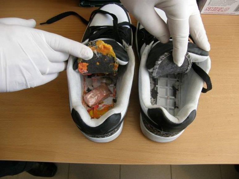 Pareigūnai tikrindami perduotus daiktus sportinių batų paduose rado vieną paketėlį su tabletėmis bei keturis paketėlius su žalsvai rusvos spalvos augalinėmis medžiagomis, kaip įtariama narkotinėmis medžiagomis.