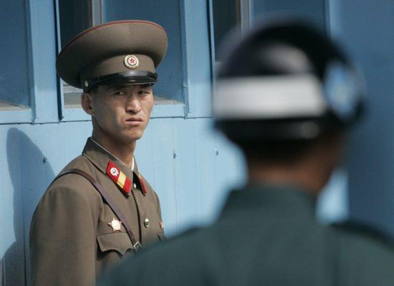 Šiaurės Korėjos kareivis (kairėje) ir Pietų Korėjo kareivis saugo Panmunjomo kaimą, kuris skiria šias dvi šalis.
