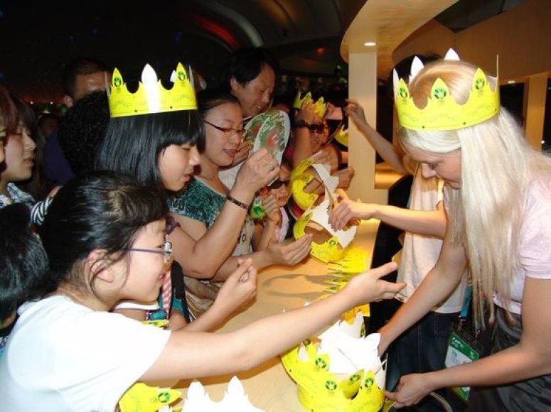 """Minint Valstybės – karaliaus Mindaugo karūnavimo dieną """"EXPO 2010"""" parodoje Šanchajuje Lietuvos paviljono lankytojams įteikiamos simbolinės popierinės karūnos."""