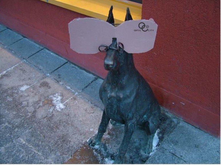 """Akiniais pasipuošė ir bronzinis šuo, """"budintis"""" prie """"Optic City"""" salono."""