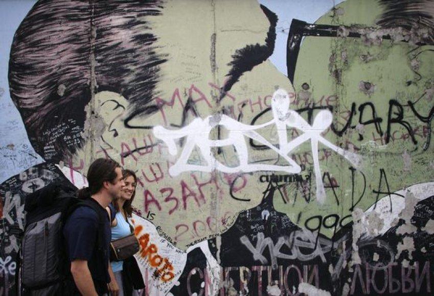 Vienas garsiausių piešinių ant Berlyno sienos, kuriame vaizduojami besibučiuojantys buvusios Rytų Vokietijos lyderis Erichas Honeckeris ir tuometinis Sovietų sąjungos vadovas Leonidas Brežnevas, dėl nuolatinių sienos valymų išbluko.