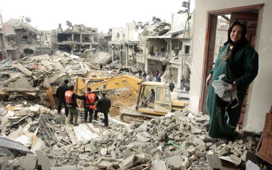 Moteris stovi prie sugriuvusių po antpuolių namų Gazos ruože.