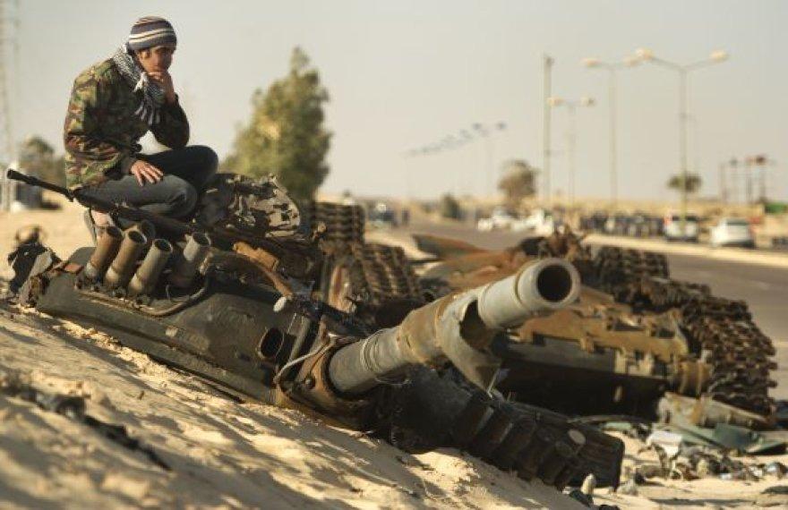 Sukilėlis tupi ant sunaikinto tanko prie Adždabijos.