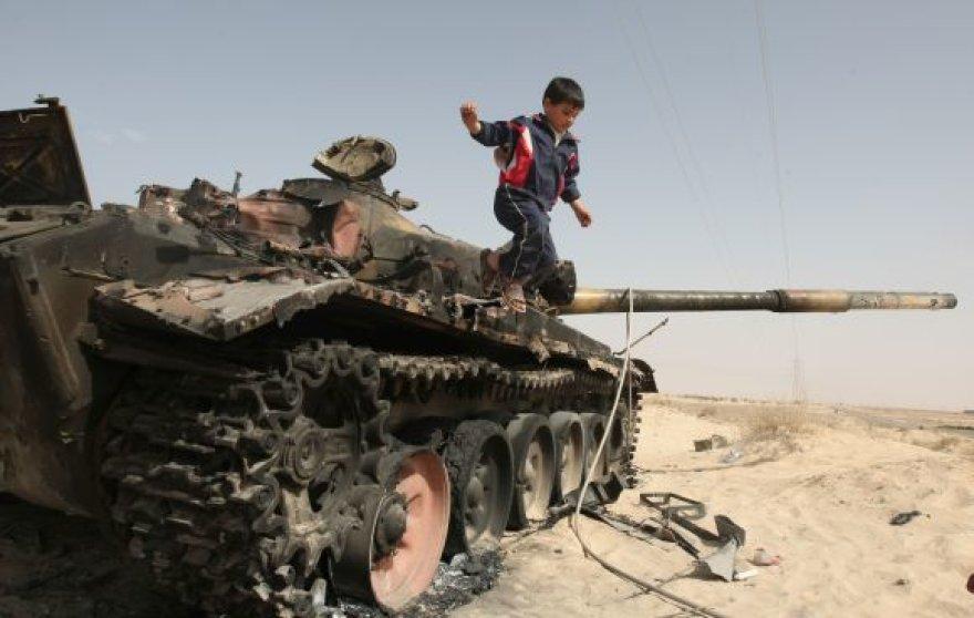 Vaikas žaidžia ant susprogdinto tanko liekanų prie Adždabijos.