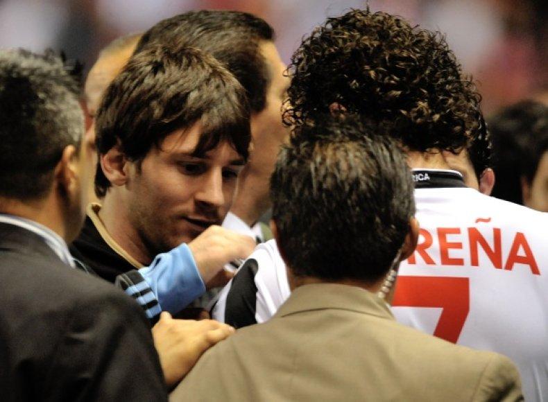 Lionelis Messi pasirašinėja ant Kosta Rikos futbolo rinktinės nario marškinėlių.