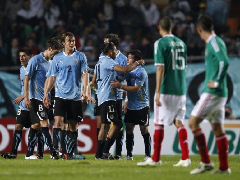 Urugvajaus futbolininkai džiaugiasi pergale.