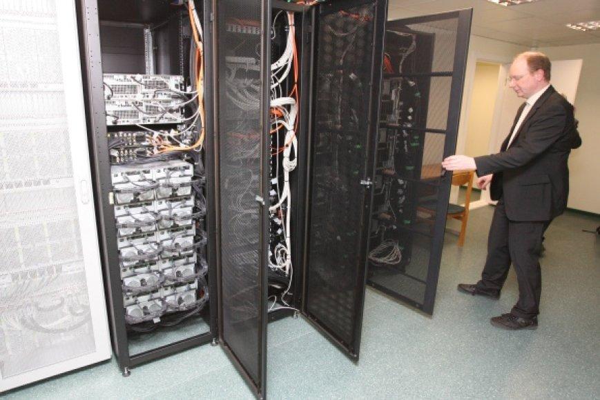 """R.Naujikas demonstruoja gausybe jungčių, laidų bei kabelių sujungtus superkompiuterio """"vidurius""""."""