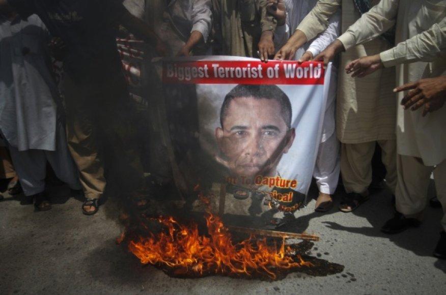 """Musulmonų aktyvistai, smerkiantys """"al Qaeda"""" lyderio Osamos bin Ladeno nužudymą, degina plakatą su JAV prezidento Baracko Obamos atvaizdu."""