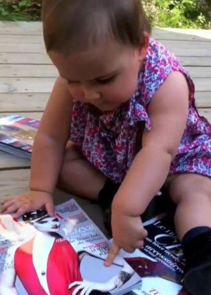 Vienerių metų vaikas atrodo nustebęs dėl to, kad žurnalo puslapiuose neveikia lietimui jautraus ekrano funkcijos.