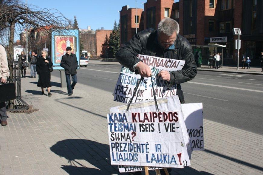 Į piketą Klaipėdoje kai kurie piketuotojai atsinešė krūvas plakatų ir ilgai ieškojo tinkamų šiam.