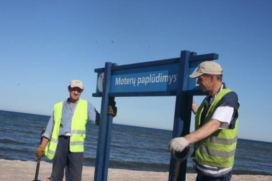 """Bendrovės """"Vakaru švara """" darbuotojai savaitgalį sudėliojo paskutinius paplūdimio ženklus."""