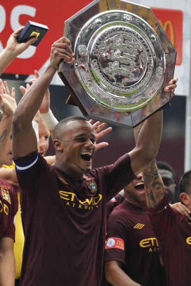 """""""Manchester City"""" kapitonas Vincentas Kompany kelia trofėjų virš galvų."""