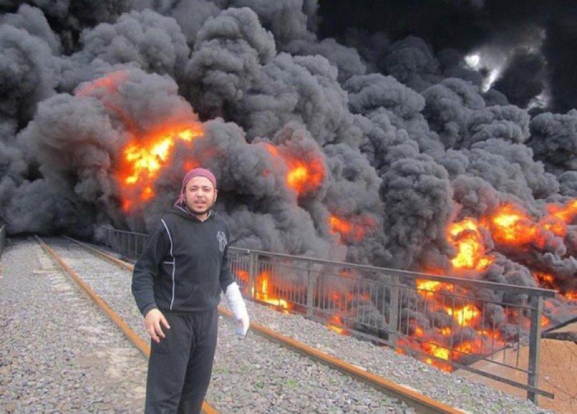 Vyras stovi netoli degančio naftotiekio Homse.