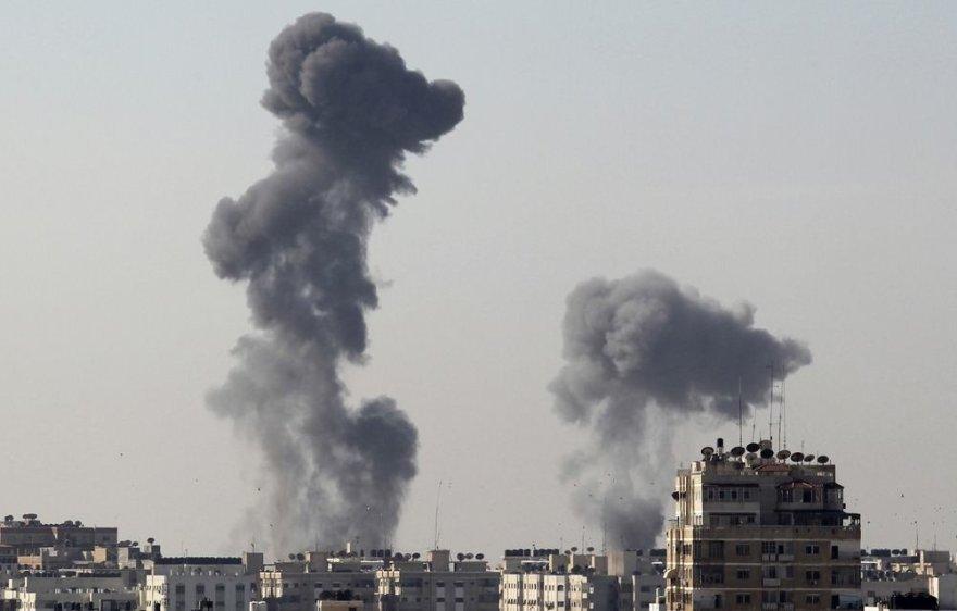 Po raketų sprogimų kyla dūmai virš Gazos miesto