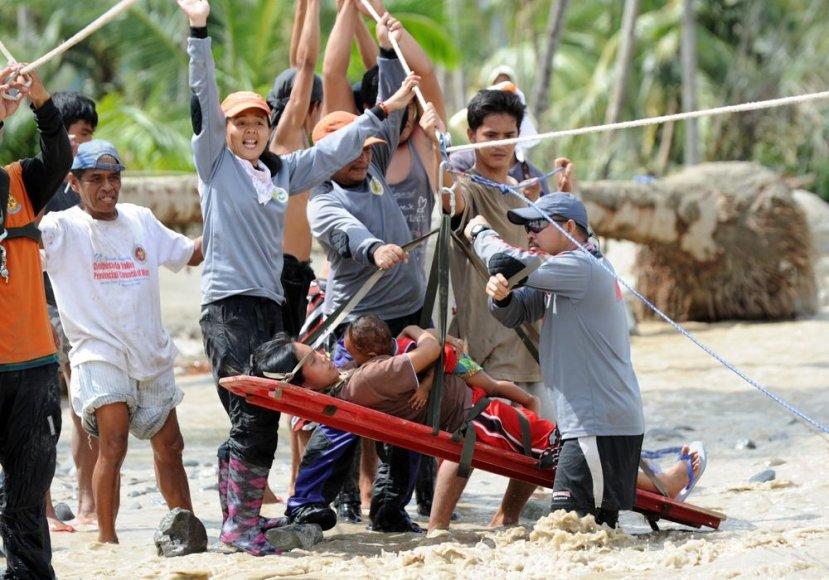 Iš apsemtos vietovės evakuojama motina su vaiku.