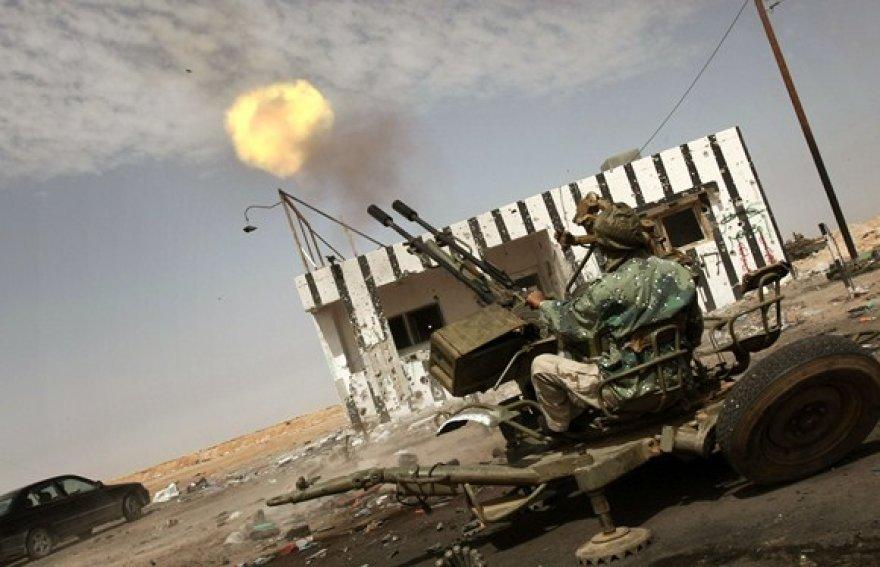 Libijos sukilėlis šaudo su priešlėktuviniu ginklu.