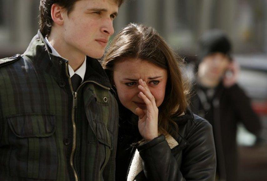 Susigraudinusi mergina su draugu netoli metro stoties