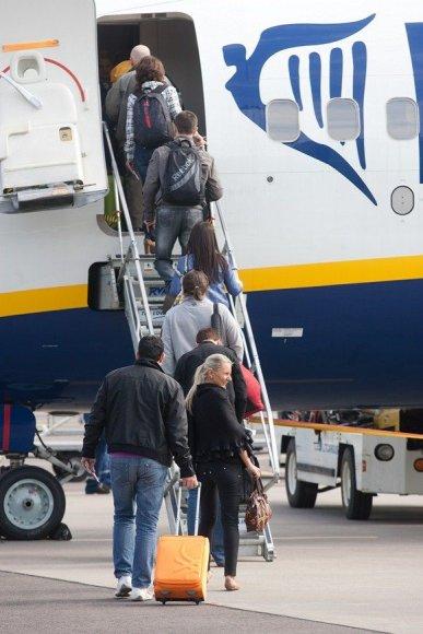 Į lėktuvą lipantys keleiviai.