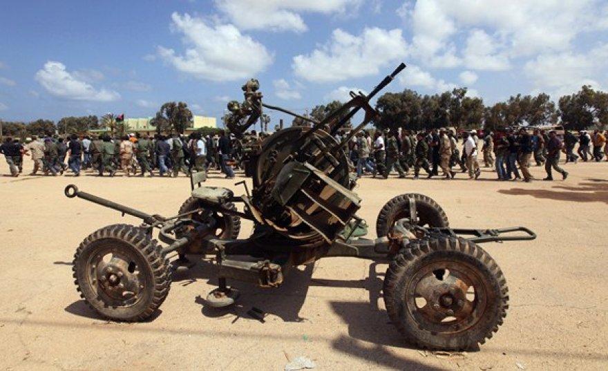 Priešlėktuvinio ginklo fone žygiuoja būsima Libijos sukilėlių armija