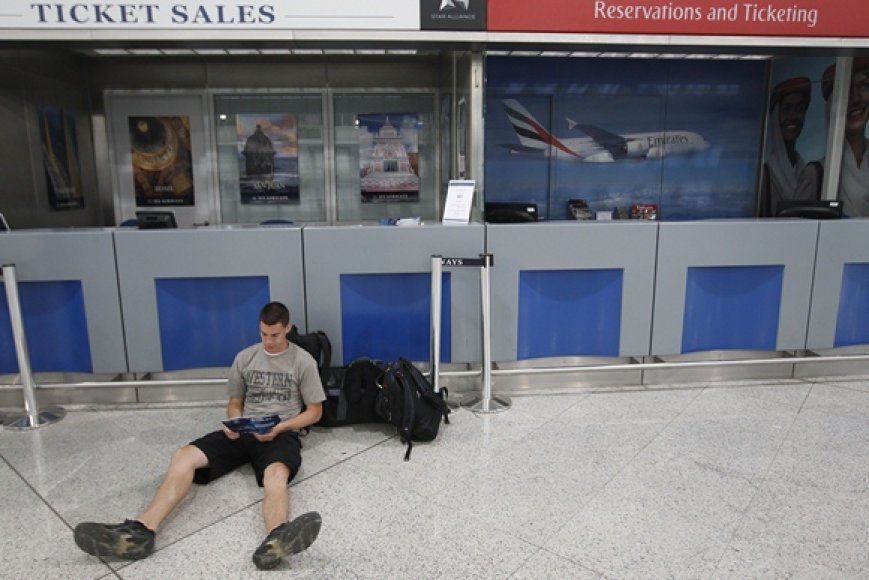Vyras Atėnų oro uoste skaito žurnalą.