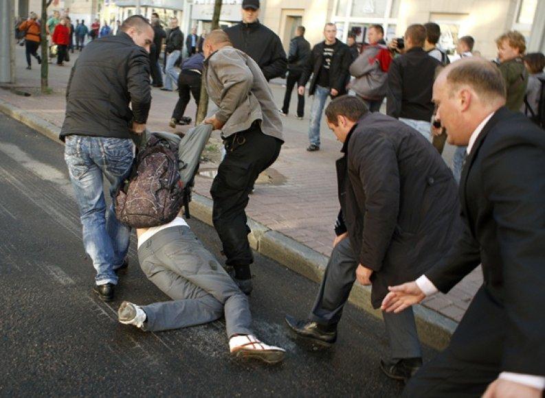 Civilių drabužiais apsirengę milicininkai tempia vyrą.