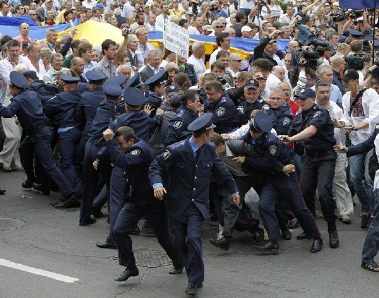 Policininkai bėga nuo protestuotojų.