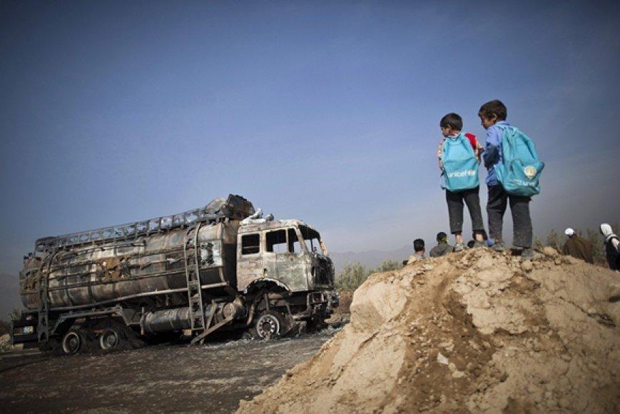 Vaikai stovi netoli sudegusio benzinvežio