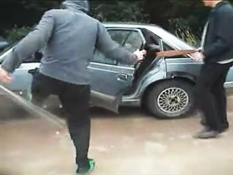 Vyrai niokoja automobilį.