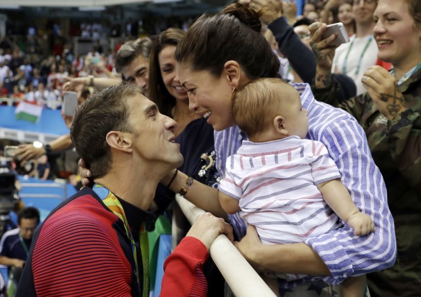 """""""Scanpix""""/AP nuotr./Michaelą Phelpsą laimėjus dar vieną aukso medalį sveikina Nicole Johnson ir jų sūnus Boomeris"""