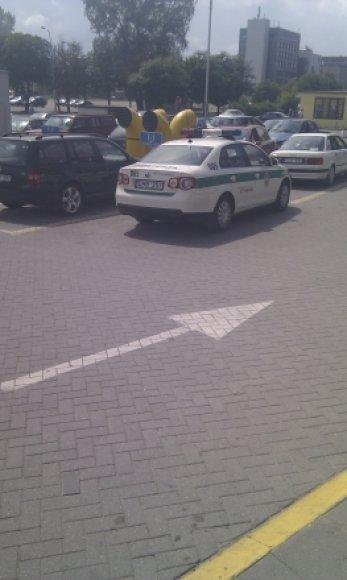 Policininkų automobilis prie geltonos linijos