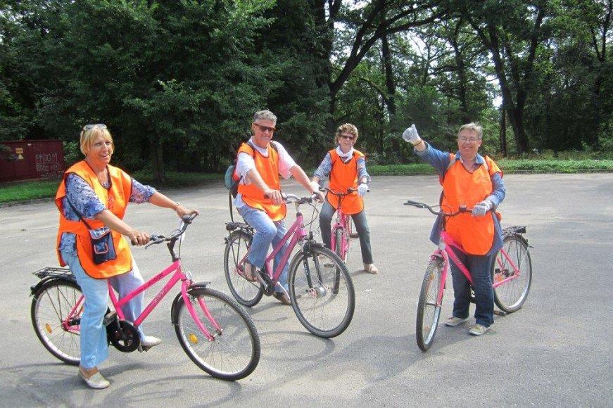 Senjorai iš Italijos rožiniais dviračiais keliauja aplink ežerus ir tvarko pakrantes.
