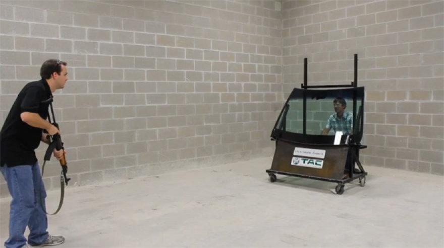 Kompanijos darbuotojas ruošiasi šauti į priekinį automobilio stiklą