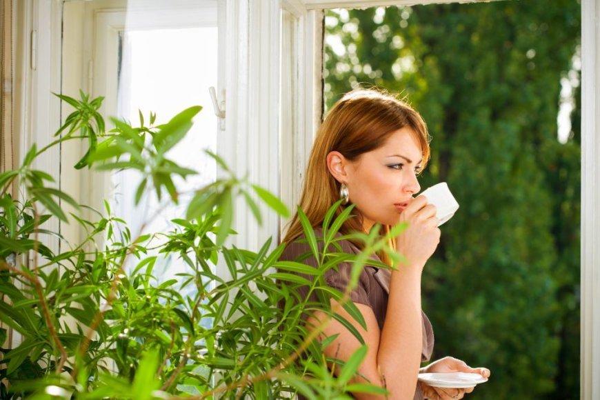 Moteris terasoje tarp augalų