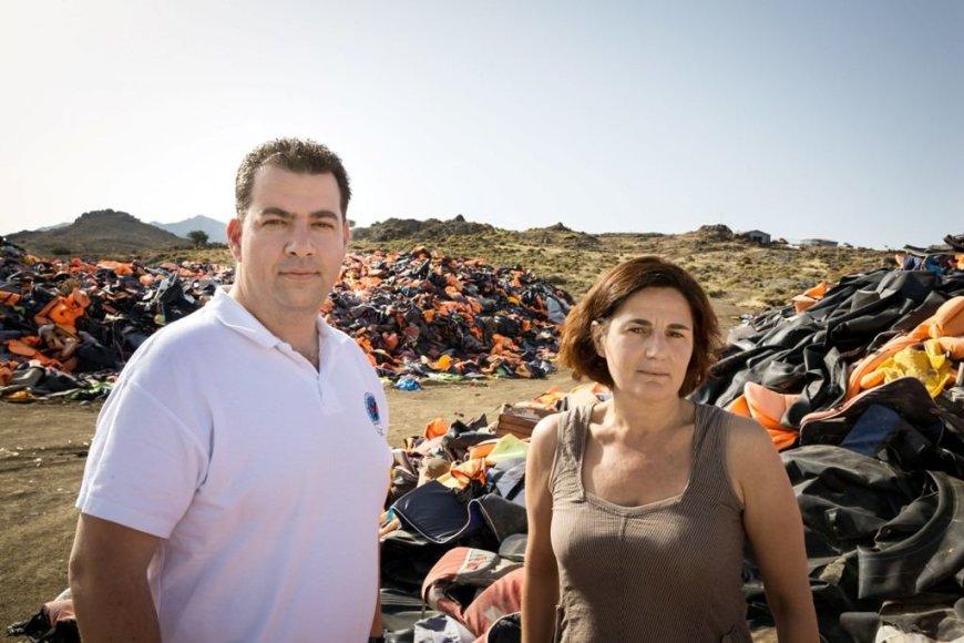 UNHCR nuotr./Nanseno pabėgėlių apdovanojimo laureatai – E.Latsoudi ir K.Mitragas – stovi Lesbo salos šiaurinėje pakrantėje. Jiems už nugarų – didžiulės, 5 m. aukščio gelbėjimo liemenių stirtos, nusėjusios 4 ha teritoriją, primenančios 2015 m. pabėgėlių krizės mastą Graikijos pakrantėse.