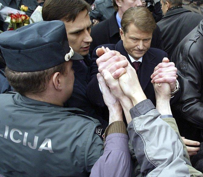 """AFP/""""Scanpix"""" nuotr./Prezidentas Rolandas Paksas spaudžia jį palaikančių žmonių rankas prie Seimo 2004 metų balandžio 6 d."""