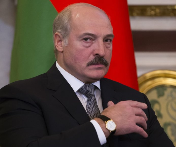 Belarus' President Alexander Lukashenko looks at the media as he listens to Russian President Vladimir Putin during their meeting in Moscow's Kremlin, Russia, Wednesday, Dec. 25, 2013. The two ex-Soviet neighbors signed agreements on military-technical cooperation and information security following