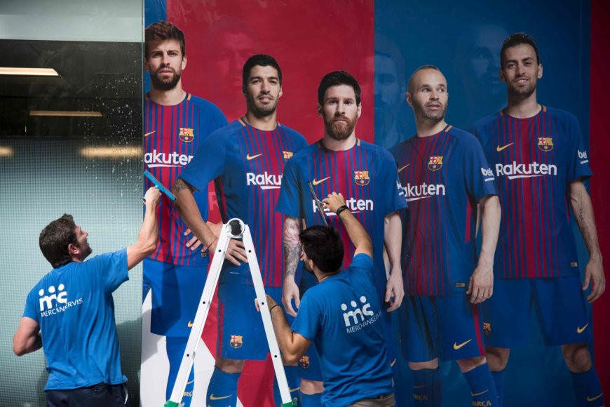 """""""Scanpix"""" nuotr./""""Barcelona"""" darbuotojai kabina komandos plakatą prieš naują sezoną – jame nebėra Neymaro."""