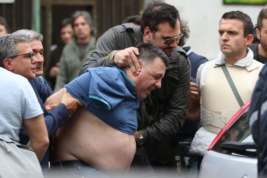Pareigūnai veda sulaikytą įtariamąjį.