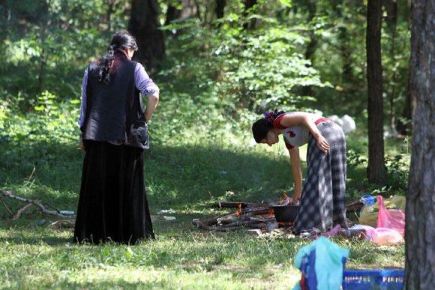 Nelegalioje stovyklavietėje moterys ruošia maistą