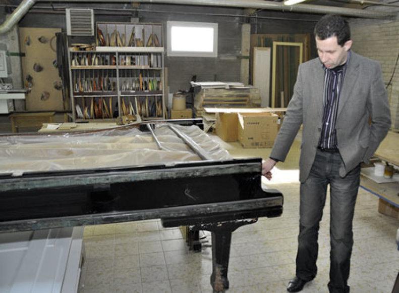 """Bendrovės """"Pirklio baldai"""" direktorius Artūras Slušnys didžiuojasi, kad jų įmonei patikėta restauruoti šį senovinį muzikos instrumentą."""
